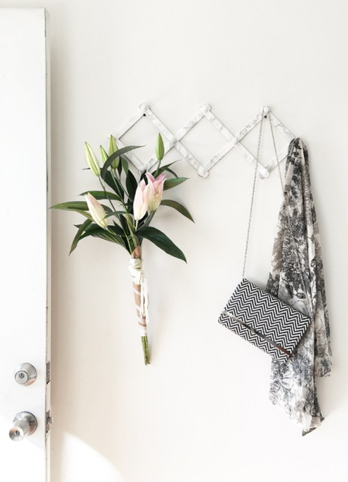 Flowers, a handbag and a shawl hanging on a marble-colored accordion rack attached to the wall.