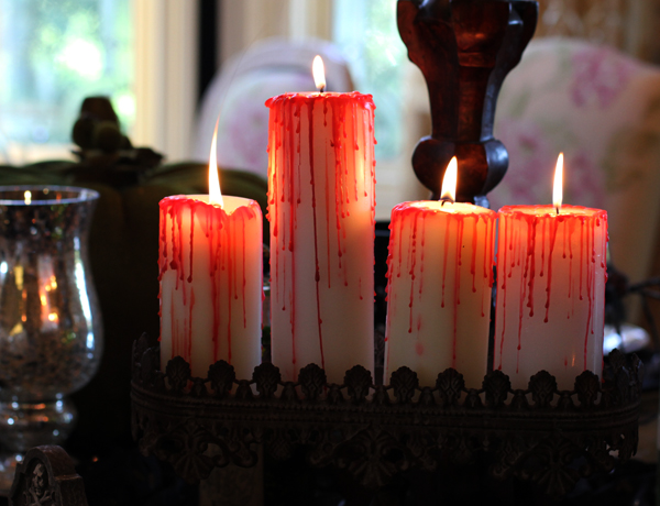 Four candles with red wax dripped on them to mimic blood.