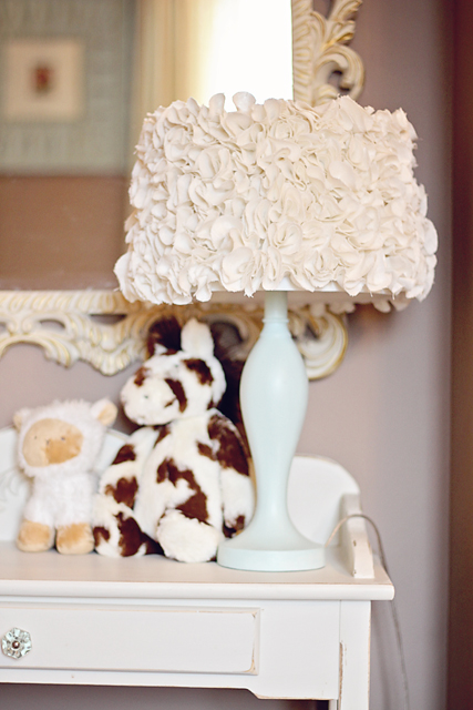 A lamp and lamp shade that has a pluffy design made from lots of pieces of heavy linen.