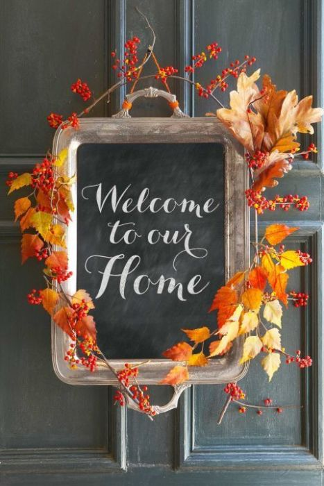"A chalkboard with the words ""Welcome to our Home"" on it with leaves and berries around the outside of it."