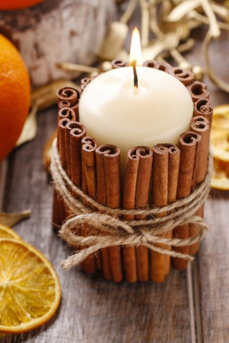 A lit candle wrapped in cinnamon sticks and tied together with string.