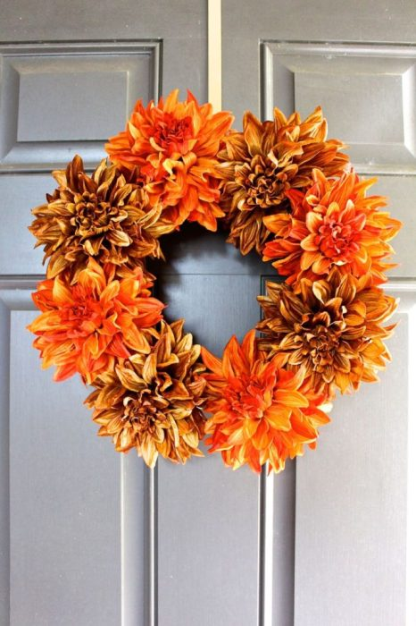 An orange-colored DIY wreath attached to a front door.