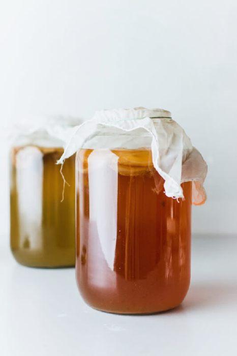 Two covered jars of kombucha