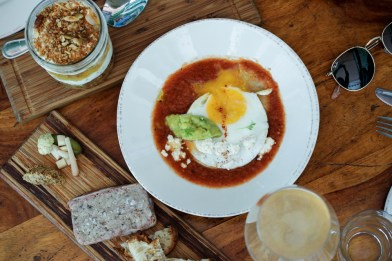 Huevos Rancheros – fried egg in salsa roja, sprinkled with housemade queso fresco and cilantro atop a Taquiza soaked tortilla