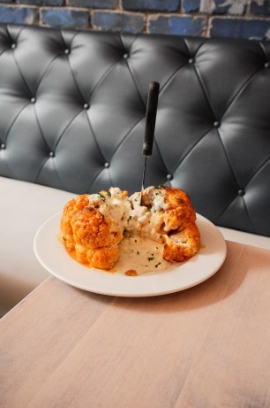 Buffalo Heirloom Cauliflower baked in our homemade buffalo sauce, topped with chives and our very own blue cheese dr