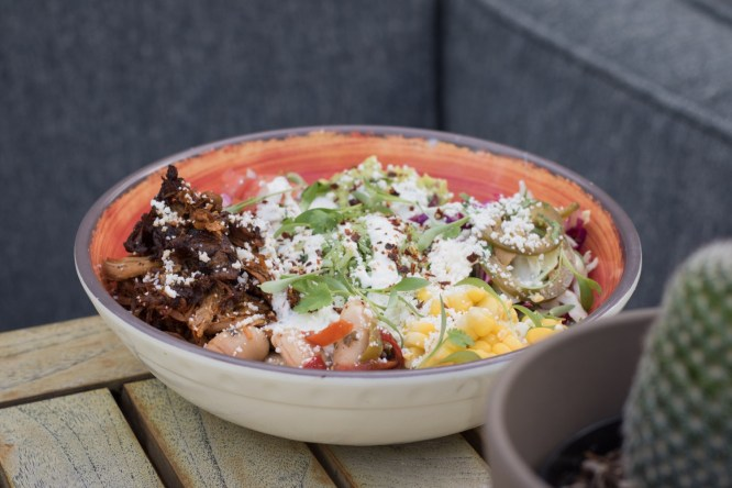 Burrito Bowl w/ short rib, gigante beans, vegetable salpicon, arroz verde, queso, corn, crema picante, guacamole