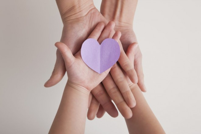 A mother and child hold a paper heart together