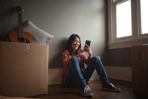 a girl sitting looking at her phone smiling | Chattanooga Home Inspector | moving made easy Chattanooga