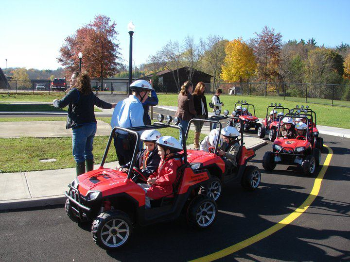 Students riding our miniature cars around the village