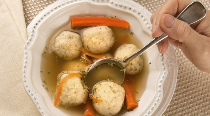 Closeup of a hand dipping a spoon into a full bowl of matzah ball soup with carrots