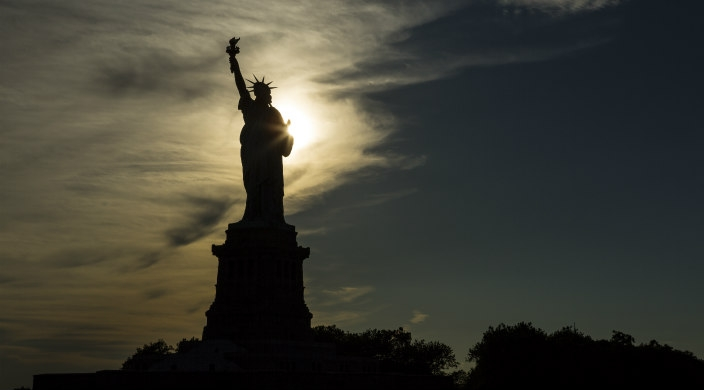 Statue of Liberty in shadow with sun shining behind her