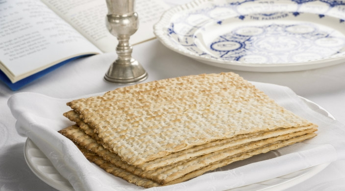 CLoseup of a seder table including a plate of matzah and an ornate matzah covering with a Kiddush cup in the background