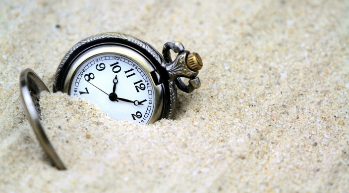 Pocketwatch partially buried in sand