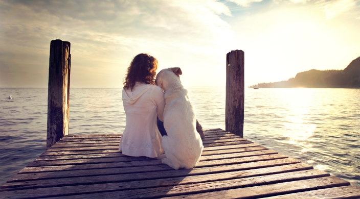 Woman and dog sitting on dock facing the water at sunset