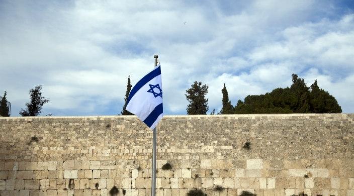 Israeli flag in front of Jerusalem stone at the Kotel