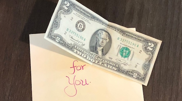 Envelope containing a note from Renee and a two dollar bill