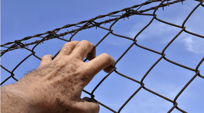 A mans hand clutching at a barbed wire fence against a blue sky