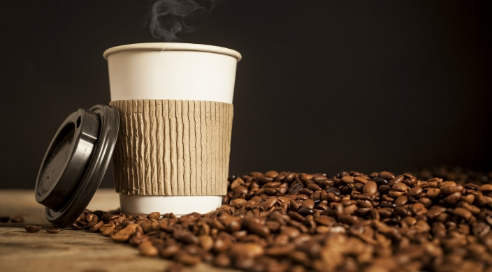 Disposable coffee cup (with steam rising from it), sleeve and lid sitting in a pile of coffee beans