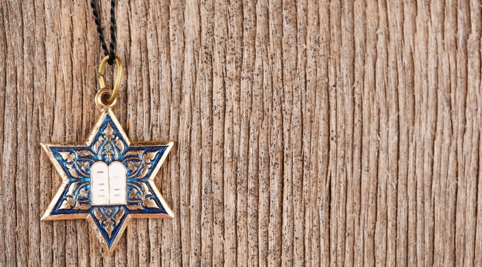 Colorful Jewish star and Ten Commandments charm on black cord suspended in front of light brown bark-like background