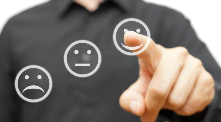 Man in black shirt pointing at smiling emoji, not at the sad or middle-of-the-road emojis.