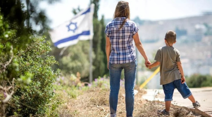 A woman holds a young childs hand with their backs toward the camera and an Israeli flag in the distance behind them