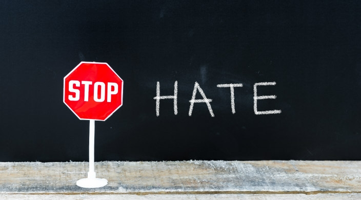Stop sign next to the word HATE written on a chalkboard