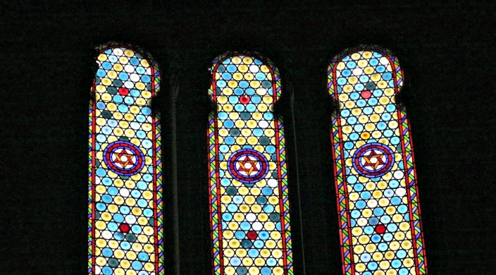 Three stained glass windows bearing Stars of David against an all black background
