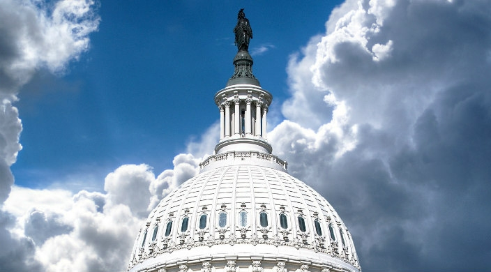 Dome of the US Capitol Building against a blue sky with clouds