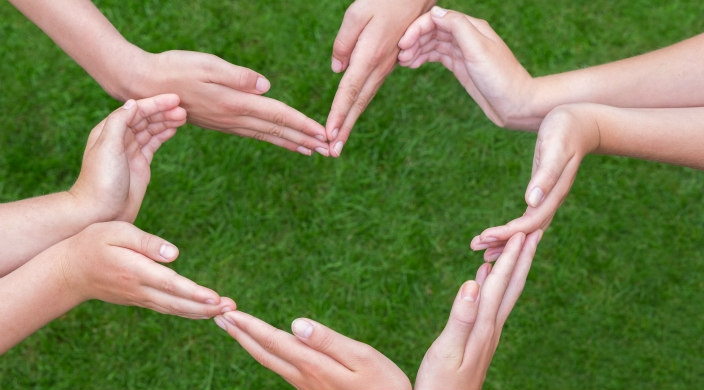 Four pairs of hands forming the outline of a heart