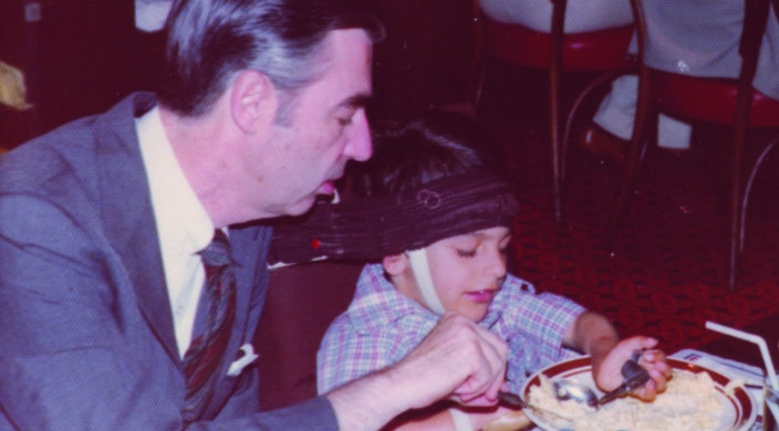Mr. Rogers helping Jeff Erlanger with breakfast of scrambled eggs
