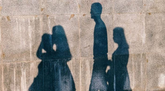 Shadows of a four person family cast upon a cement wall