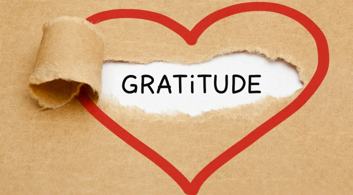The word gratitude revealed when butcher paper is torn away; the whole graphic is outlined with a heart-shaped red line