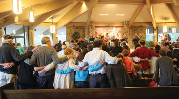 Congregants welcoming Shabbat with arms linked together