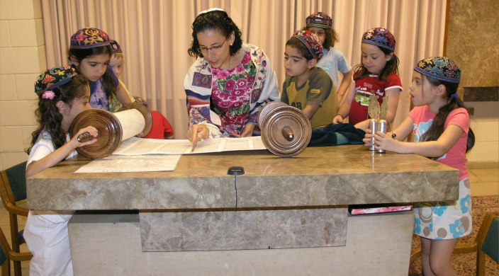 Young children gathered around watching a woman read from a Torah scroll