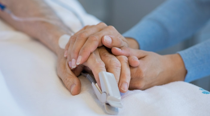 Hospital visitor clasping the hand of hospital patient in bed