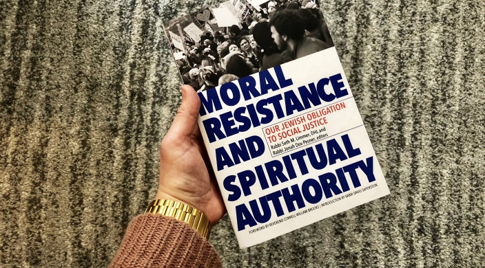 Hand in a pink sweater holding the new Moral Resistance book