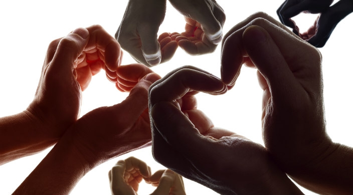 Many pairs of hands forming hearts