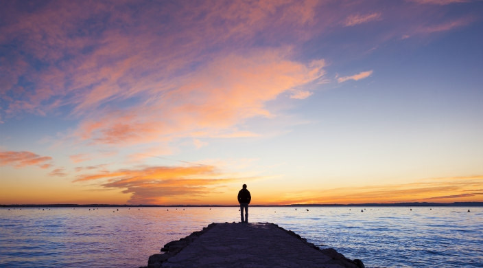 Man standing at the end of a pier during sunset