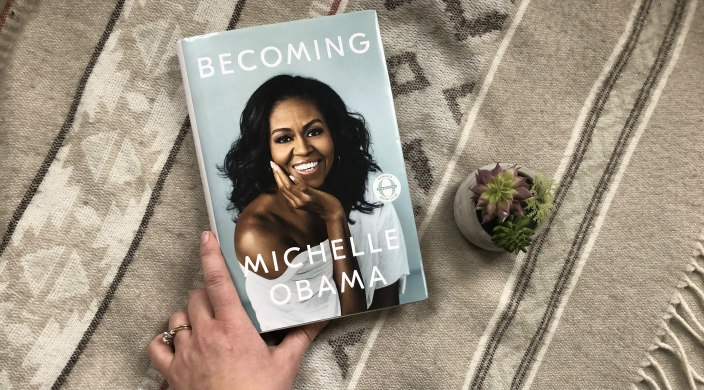 Hand reaching toward Michelle Obamas book Becoming