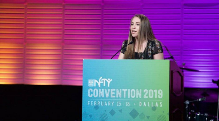 Sarah Friedman stands at a podium bearing the name NFTY Convention