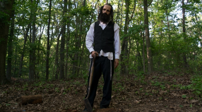 Movie still of an Orthodox Jewish man holding a shovel and standing atop a mound of dirt as if digging a grave