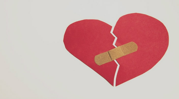 Construction paper rendering of a broken heart held together with a bandage