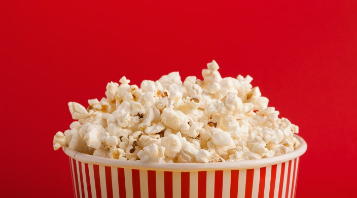 Overflowing bucket of popcorn against a red background