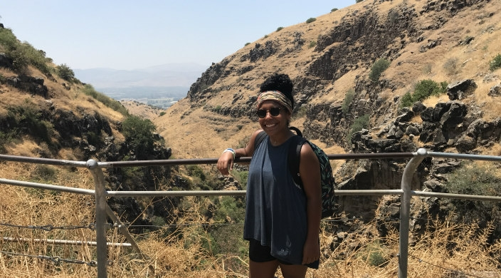 The author smiling while standing in front of scenery in Israel