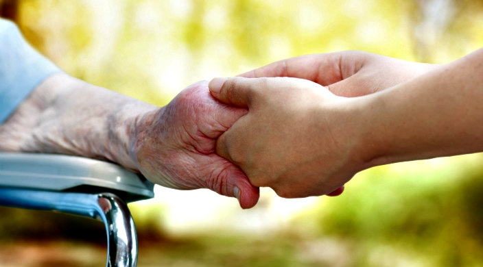 Hand of an elderly person held by the hand of a younger person