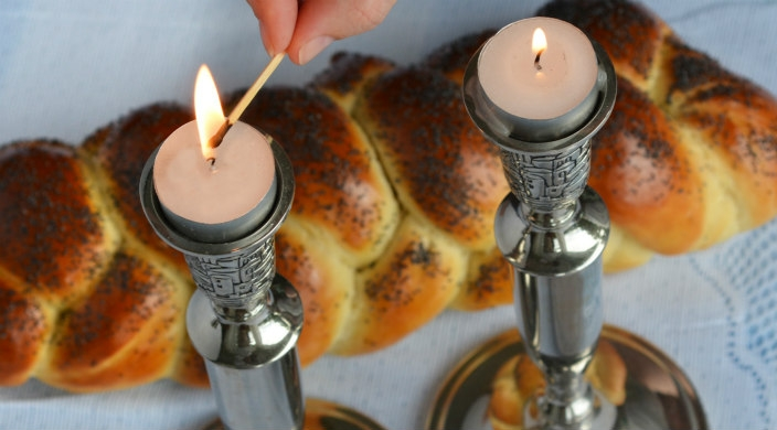 Hand lighting Shabbat candles in silver candleholders next to a challah