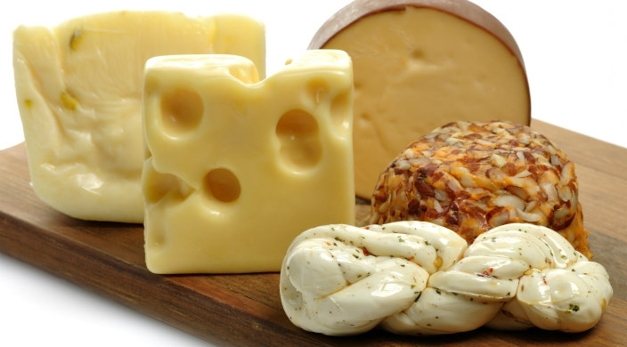 Four kinds of cheeses sitting on a wooden cheeseboard