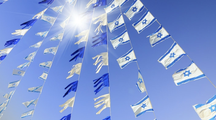 Israeli flags and blue streamers on a wire in the sunlight