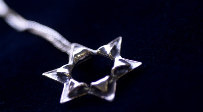 Modern style silver Jewish star on a chain with dark blue/black background