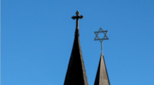 Pointed roofs of a church and a synagogue with a cross atop one and a Star of David atop the other